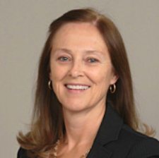 Photograph of Maureen Bellamy, presenting as a white female with long, medium brown hair. She is smiling.