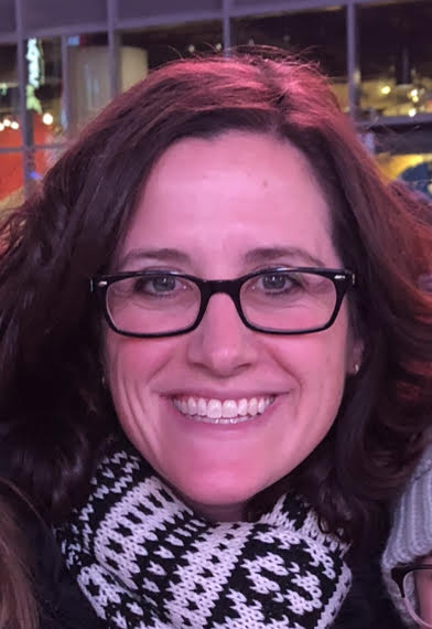 Photograph of Nicole Frye, presenting as a white female with  dark brown hair. She is wearing black-rimmed glasses and smiling.
