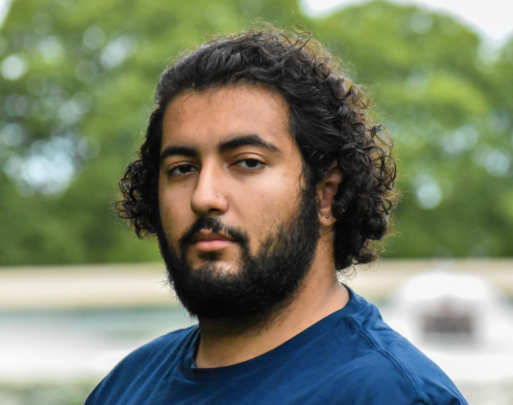 Photo of Shareef Alwarasneh, presenting as a male with light brown skin. He has curly, dark brown hair and a beard.