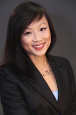 Photo of Virginia Hoang, an Asian female with long, dark brown hair. She is looking at the computer and smiling.