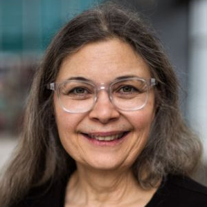 Photo of Donna Morere. Photo shows a white female with gray-brown hair and glasses.